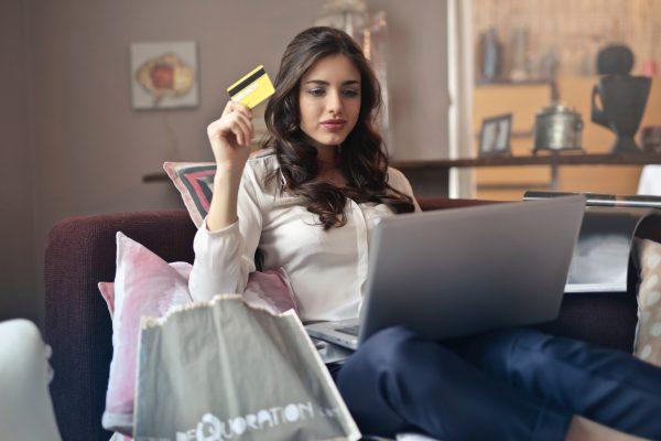 Henkilö käyttää kanta-asiakaskorttia tietokoneella sohvalla istuen.