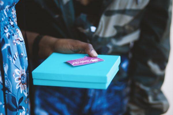 Henkilö kantaa lahjakorttia ja pakkausta.